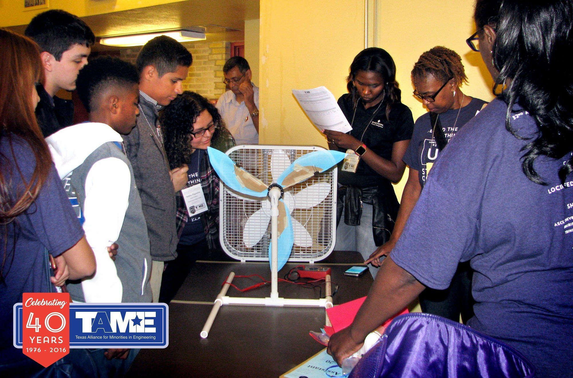 Six diverse students hold up a prototype of a Wind Turbine made from cardstock and craft supplies. From the Engineering Design Challenge at the 2017 State STEM Competition in San Antonio, TX.