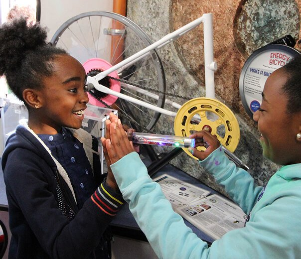 Two middle-school African American girls grin at each other while using the Energy Stick exhibit. On one side they press their palms together, and with their other hands they hold either end of a plastic cylinder with lights inside. The contact between their hands creates a circuit and the Energy stick lights up and makes a noise.