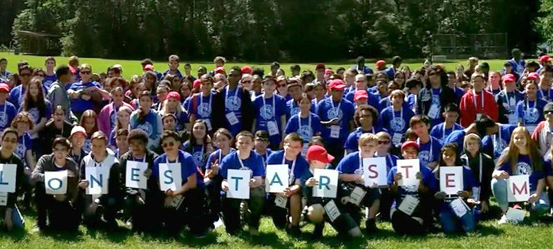 Large group of TAME students pose for a photo in a green field. Students in the front row hold signs that spell out #LonestarSTEM. From the 2019 State STEM Competition.