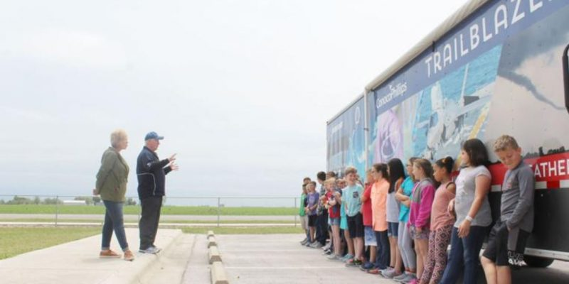 The Trailblazer Facilitator stands with a teacher to make safety announcements to a line of children leaning against a large trailer, the Trailblazer mobile STEM museum. Photo credit to Valerie Bustamante, Seguin Gazette.