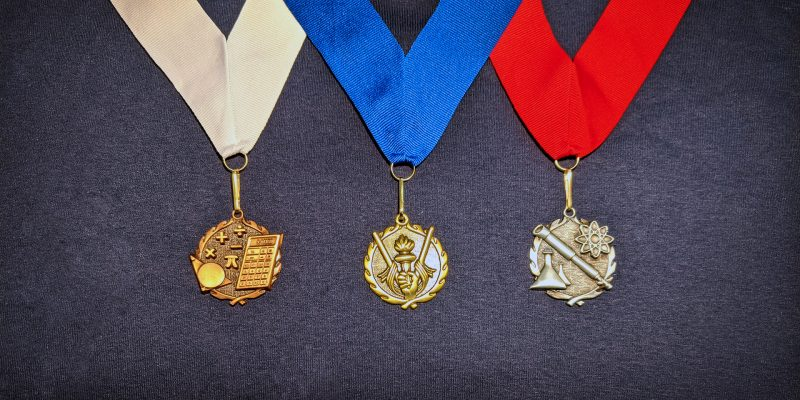 Image of three medals against navy blue fabric. On the left, a bronze medal with a white ribbon has math symbols. On the right, a silver medal with a red ribbon has science symbols. In the middle, a gold medal with a blue ribbon has a trophy.