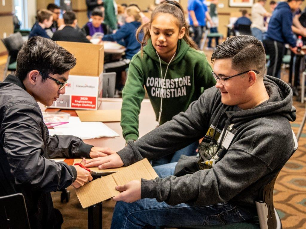 One student cuts cardboard another holds steady while a third watches, while building a prototype in the 2020 San Angelo STEM Competition.