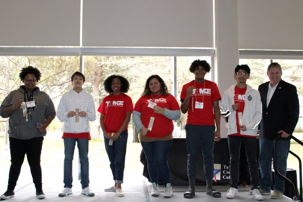 Six students wearing red TAME shirts hold up silver ribbons during the Awards Ceremony at the 2020 Dallas Divisional STEM Competition. The students' ages range from grade 6 to grade 12.