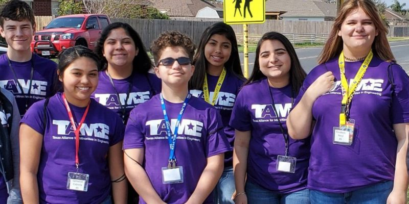 Ten middle school students in purple TAME shirts stand outside near a school.