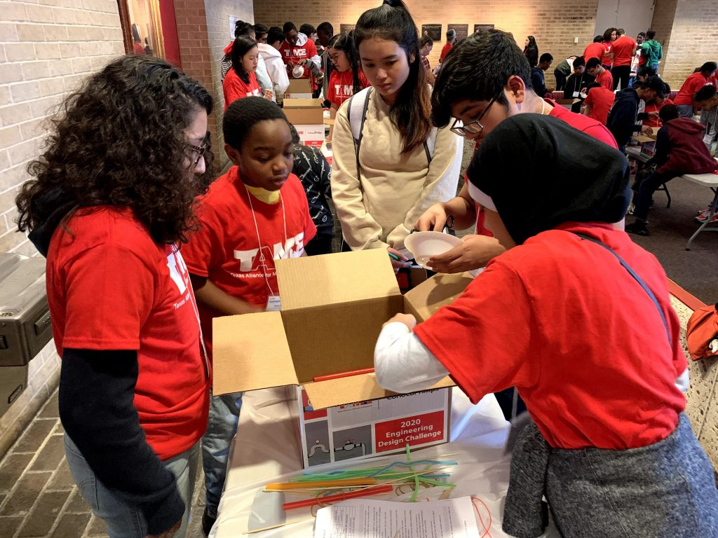 A diverse team of five students in red TAME shirts look into a box while building a prototype in the 2020 Gulf Coast STEM Competition.