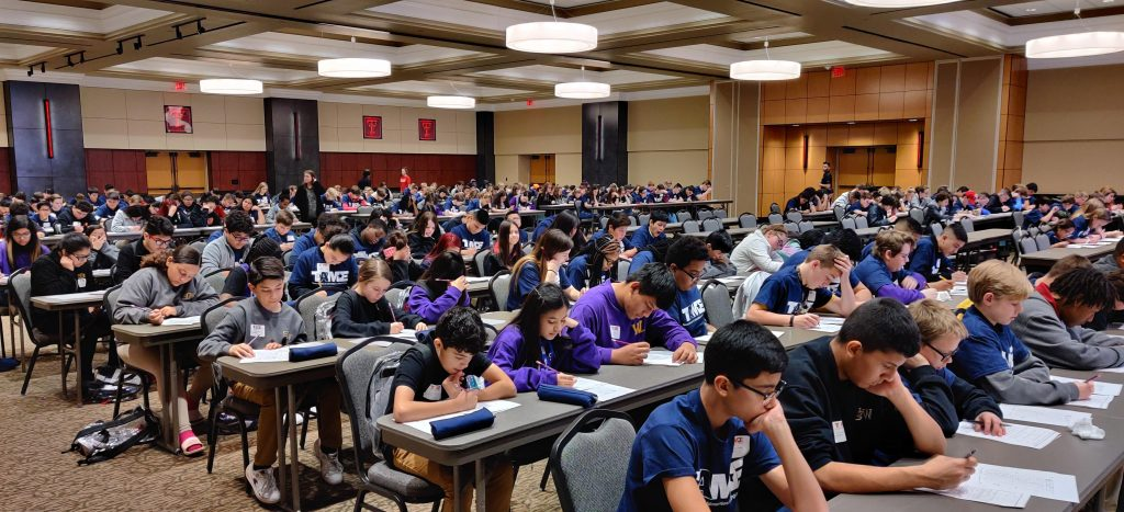 A diverse group of students wearing TAME shirts, grades 6-12, are pictured taking tests in a large auditorium with the Texas Tech University Logo on the walls.