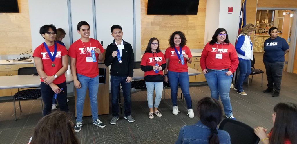 Three male students and three female students wearing red TAME shirts hold up blue ribbons during the Awards Ceremony at the 2020 West Texas Divisional STEM Competition. The students' ages range from grade 6 to grade 12.