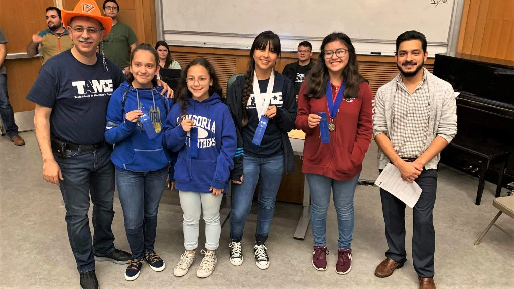 Six students wearing TAME shirts and school shirts from the Valley hold up blue ribbons during the Awards Ceremony at the 2020 Valley Divisional STEM Competition. The students' ages range from grade 6 to grade 12.