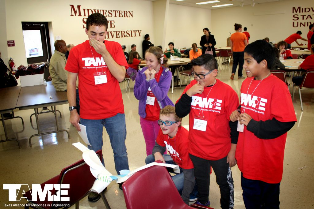 """Five students in red TAME shirts grin nervously at their airplane prototype balanced between two chairs. In the background, other students work on their prototypes, and the wall is painted with the words """"Midwestern State University."""""""