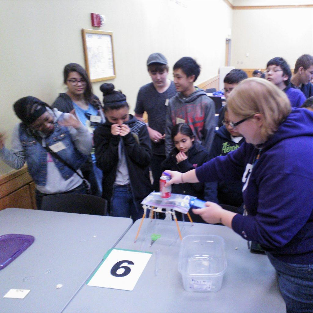 Students react as a volunteer Engineering Design Challenge Judge tests a student prototype at the 2014 Dallas Divisional Math & Science Competition, hosted at Tarrant County College.