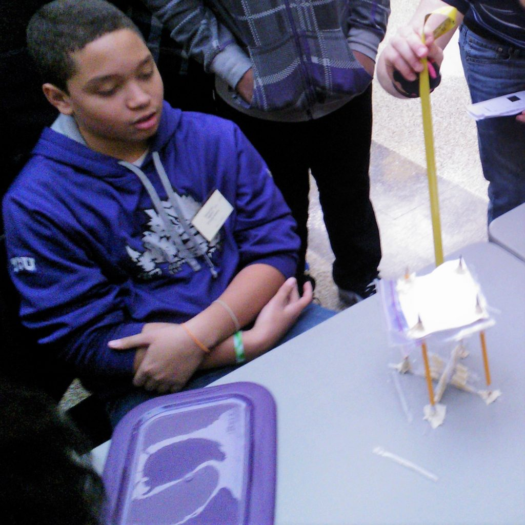 A student looks on as a volunteer Engineering Design Challenge Judge tests a student prototype at the 2014 Dallas Divisional Math & Science Competition, hosted at Tarrant County College.