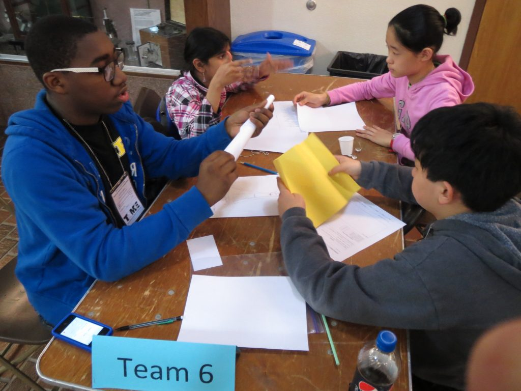 Four students of different ages work on a prototype of an Olympic Tower.