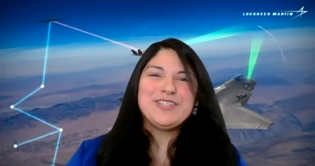 A woman with long black hair smiles during a zoom presentation, against a backdrop of fighter jets in the sky.