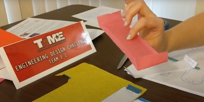A light-skinned hand with silver nails holds a red tissue paper glider that is rectangular with small wing shapes. There are supplies and paper on the table underneath.